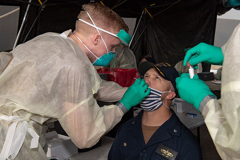 Hospital Corpsman Ethan Holder (left) takes a test sample from Cmdr. Andrew K...