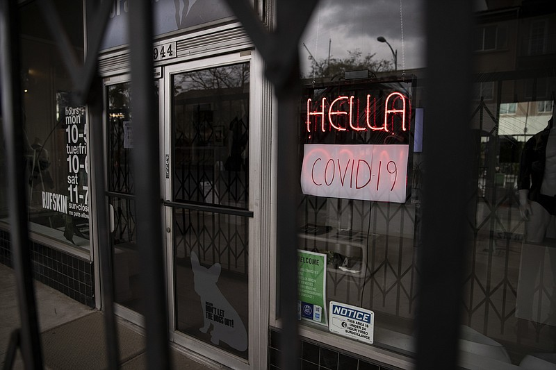 A sign blinks in the entrance of a clothing store that closed as part of effo...