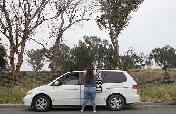 Patricia Mendoza hangs a banner on her minivan during a r...