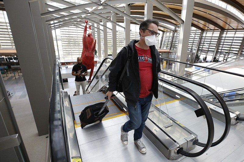 Southwest Airline passenger Robert Civettini wears a face mask as he goes to ...