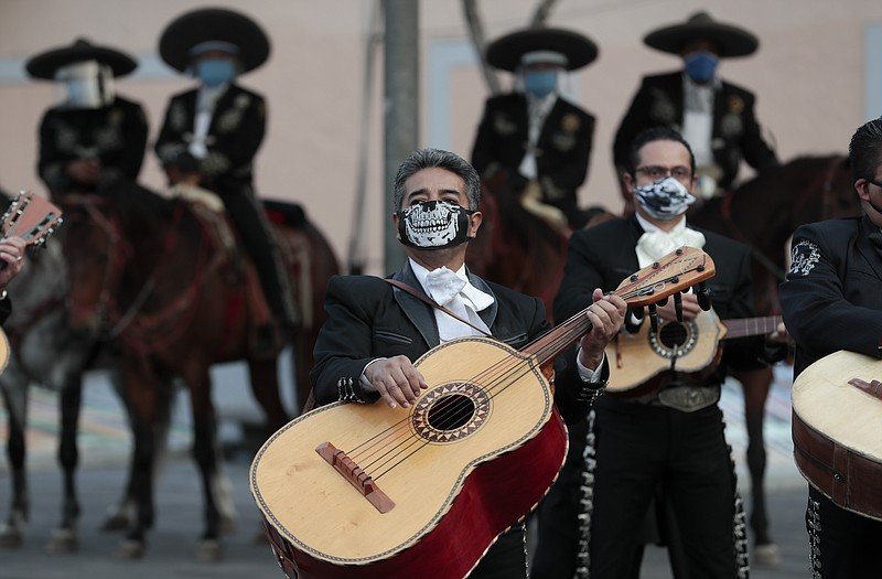 Mariachi musicians wear masks amid the new coronavirus pandemic as they play ...