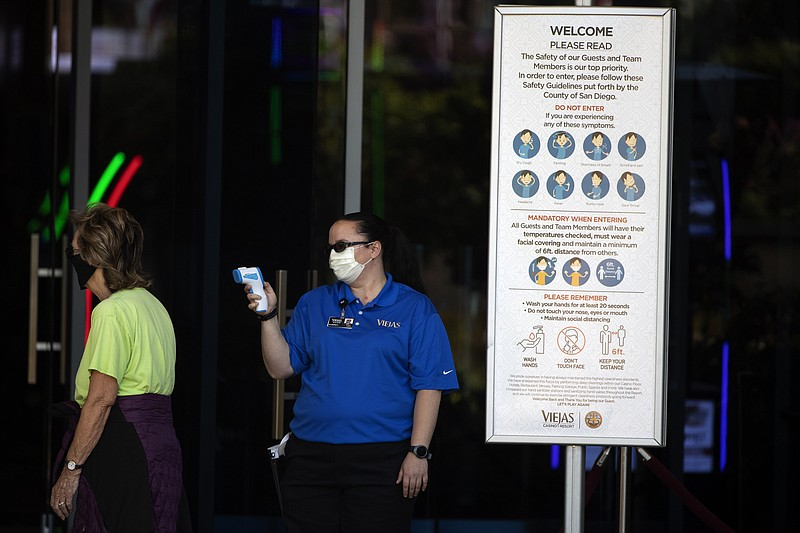 An official reads the temperature of a woman at the entrance to the Viejas Ca...