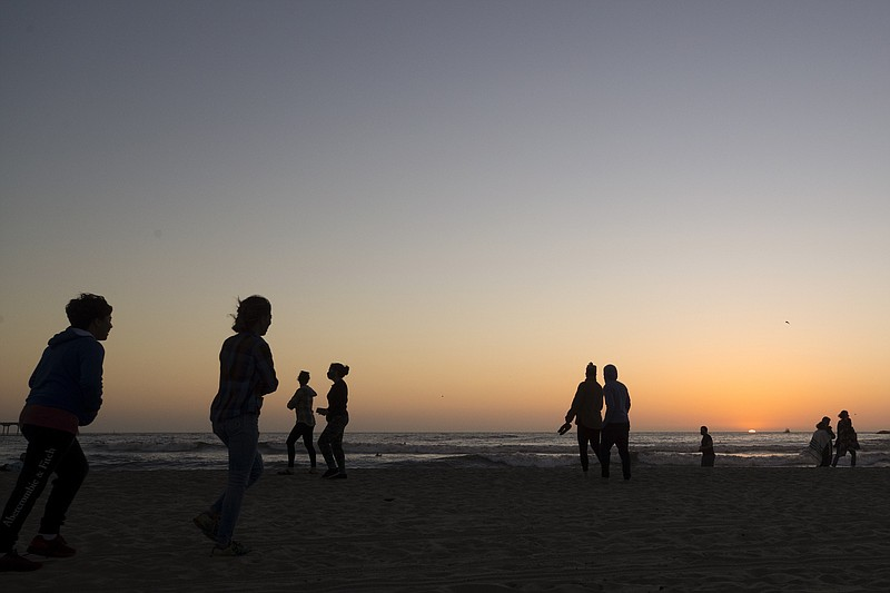 People keep apart along Ocean Beach at sunset Monday, May 4, 2020, in San Die...