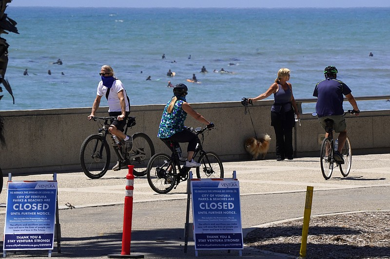 People use the bike path as surfers are seen in the background, Thursday, Apr...