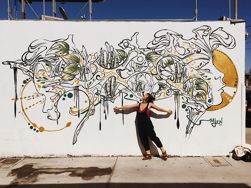 San Diego visual artist Mary Jhun is pictured with her mural in City Heights ...