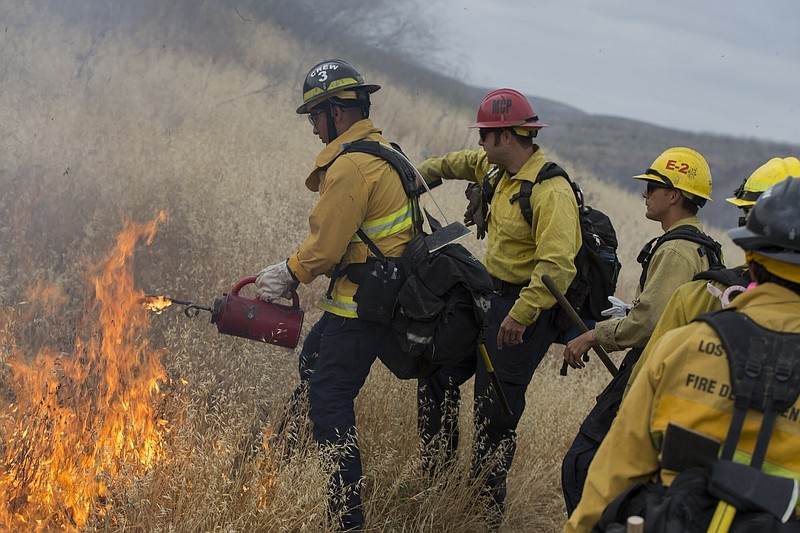 Los Angeles firefighter Ivan Del-Ril is instructed by Camp Pendleton fire cap...