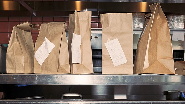 Restaurant takeout bags await customer pick-up in an Apri...