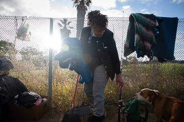 Wanita Long packs up blankets after sleeping on an area o...