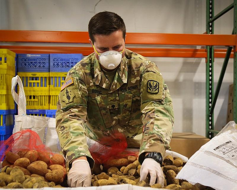 Spc. Trent Bostic of the North Carolina National Guard examines and sorts pro...