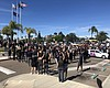 Protesters in La Mesa stand with their fists ra...