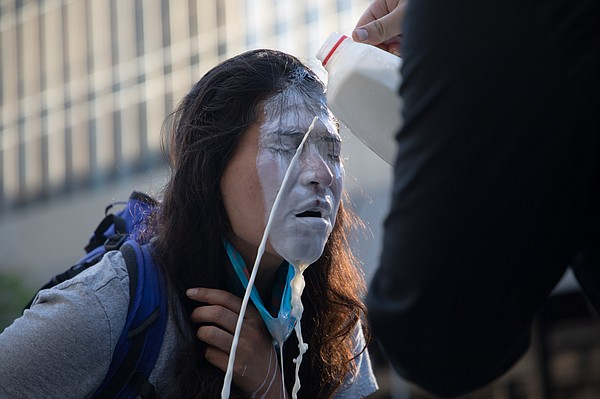 A fellow protester pours milk over a woman's face after S...