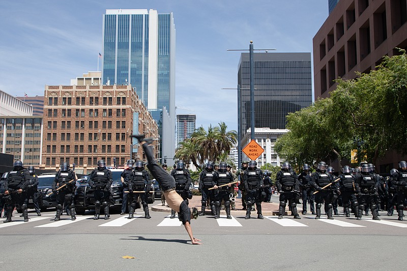 A protester does back handsprings in front of a line of San Diego police offi...