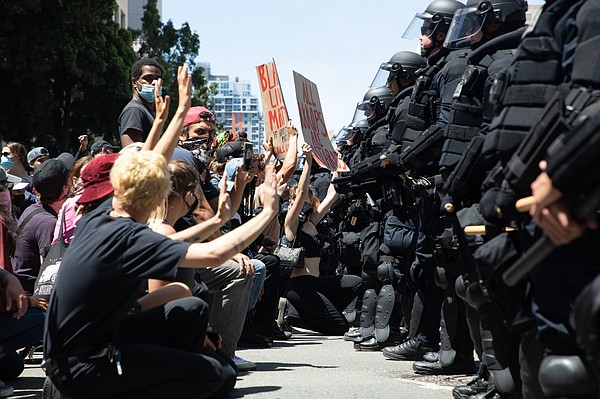 San Diego police officers block demonstrators during a pr...