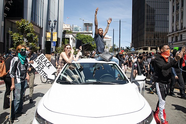 A protester drives a vehicle up to a San Diego police lin...