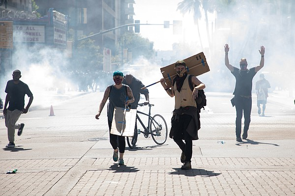 Protesters move away from the police line after San Diego...