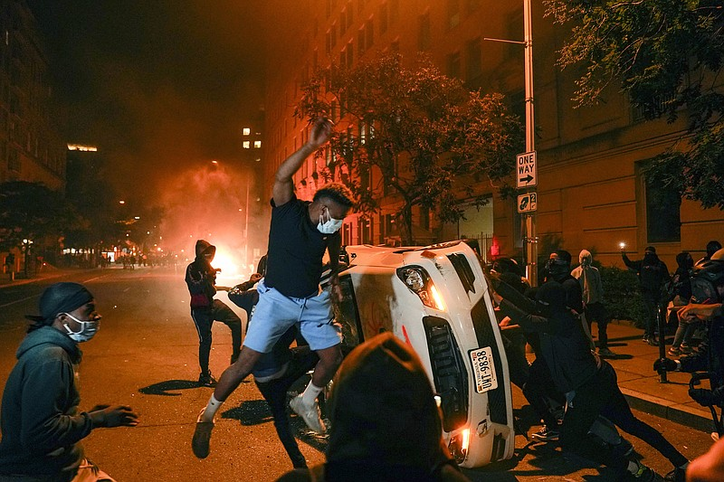 Demonstrators vandalize a car as they protest the death of George Floyd, Sund...