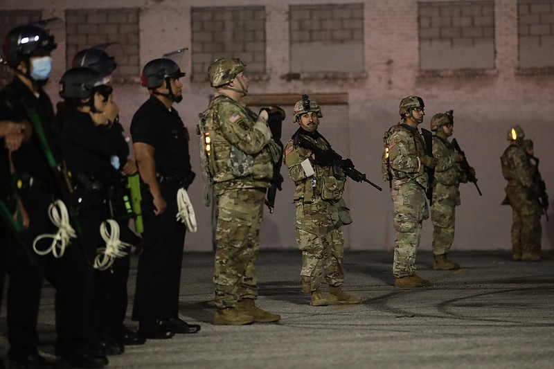National Guardsmen and Los Angeles police officers stand guard as protests ov...