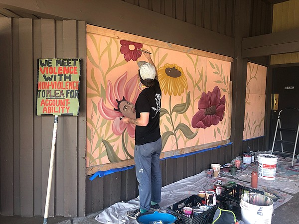 Artist Aaron Glasson paints the boards outside of Alberto...