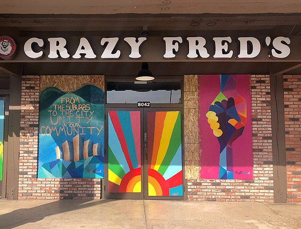 Brightly colored murals adorn the plywood boards on Crazy...