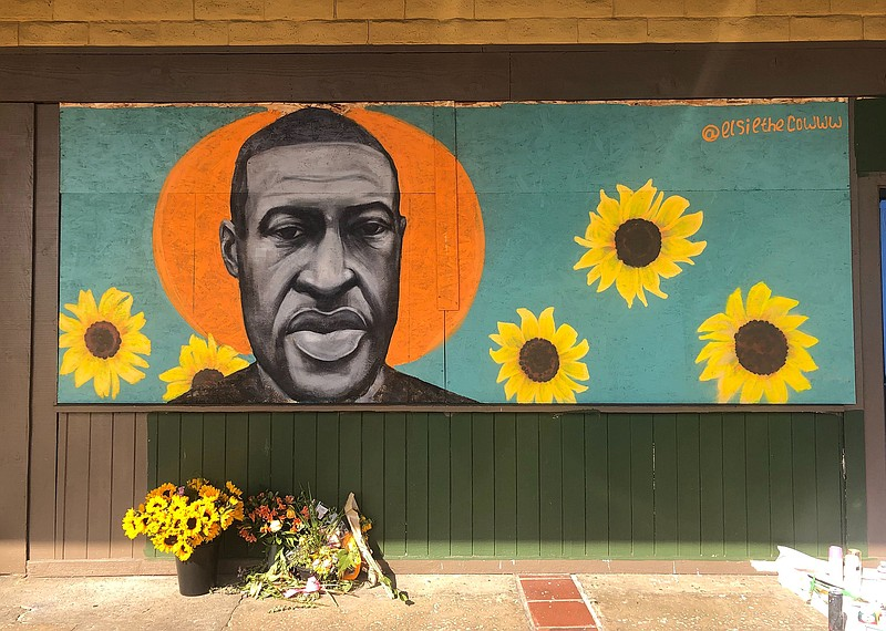 A mural of George Floyd, painted by artist Chloe Becky, covers the plywood bo...