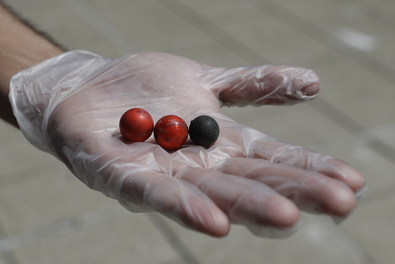 A volunteer holds rubber bullets in his hand that was collected with other de...