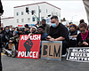 Protesters sit with signs in San Diego during a...