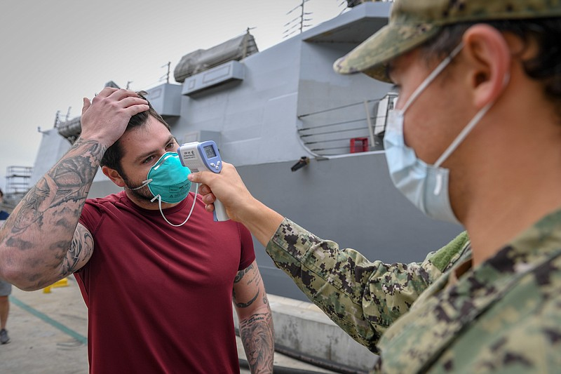 Sailor has his temperature checked before being allowed on board the USS Kidd...