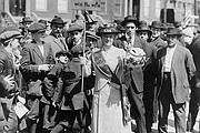 """Suffragist, """"Mrs. Suffern,"""" holding sign; crowd of boys and men behind. N.Y.,..."""