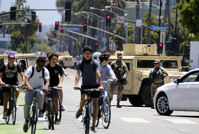 Cyclists ride down a street past a road block with National Guard troops alon...