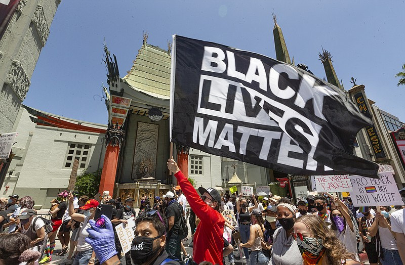 Thousands of people march past the TCL Chinese Theatre on Hollywood Boulevard...