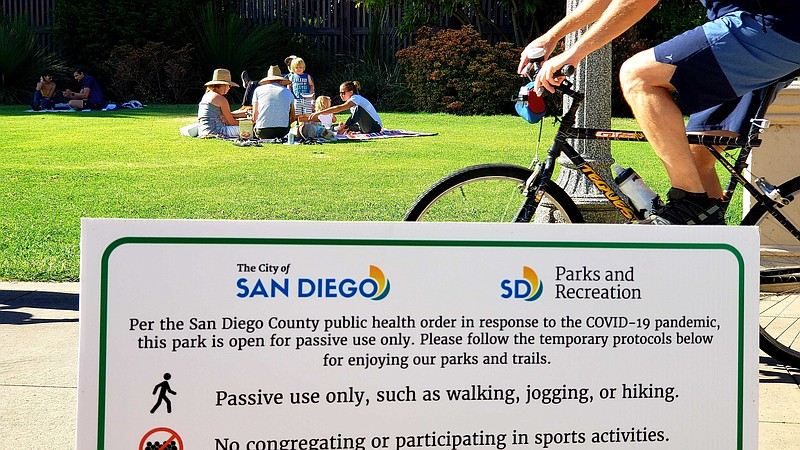 Families having picnics at Balboa Park on June 17, 2020, as a bicyclist rides...