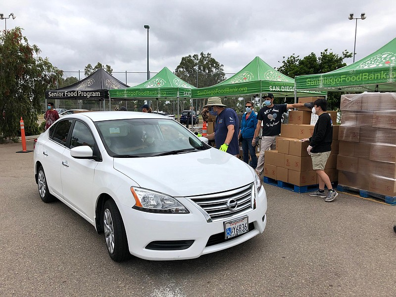 Volunteers with the San Diego Food Bank help load food into cars at the Mira ...