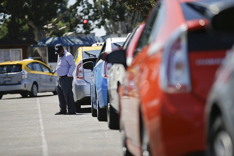 A cab driver waits near his car in line at a depot near the airport Wednesday...