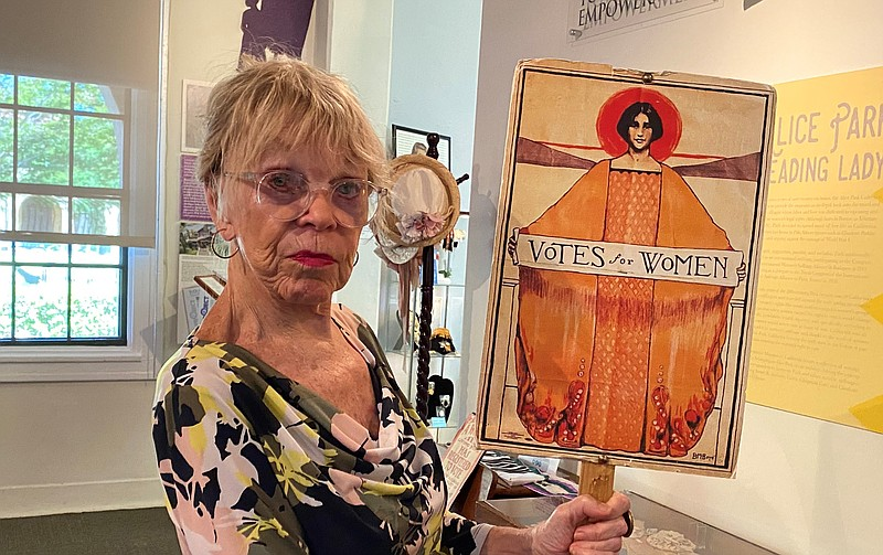 Anne Hoiberg holds a political sign for women's suffrage at The Women's Museu...