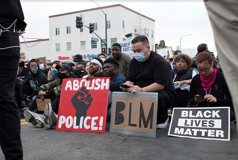 Protesters sit with signs in San Diego during a demonstration, June 5, 2020.
