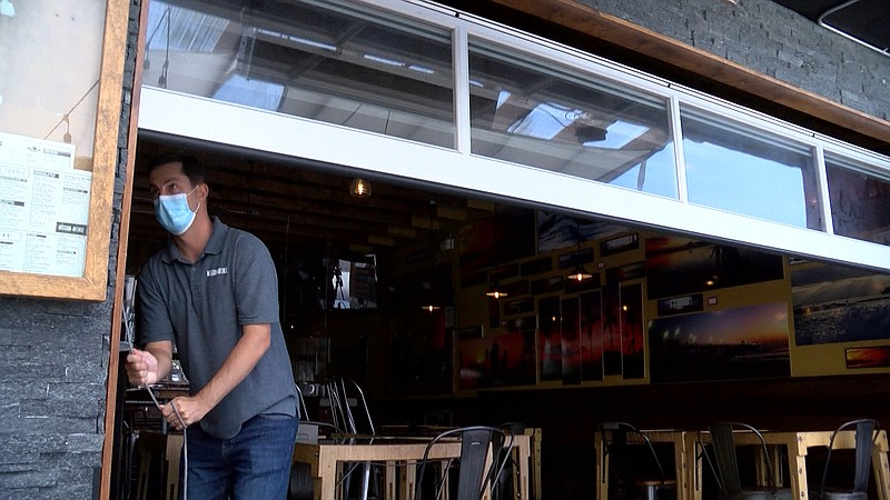 Cameron Braselton closes the patio to his Oceanside restaurant Mission Avenue...