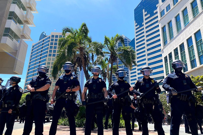 A line of police officers observe protesters during a demonstration in downto...