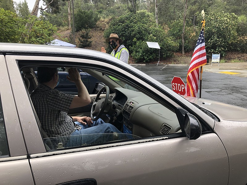 A man takes the oath to become a citizen at a drive-thru naturalization site ...