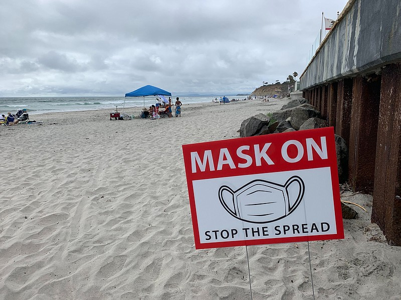 A sign requiring the use of masks to prevent the spread of COVID-19 is pictur...
