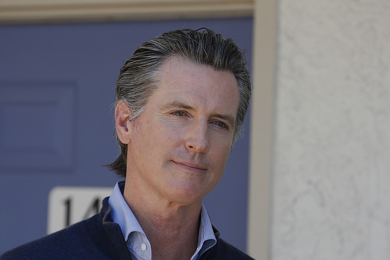 Gov. Gavin Newsom listens to a reporter's question as he gives an update on t...