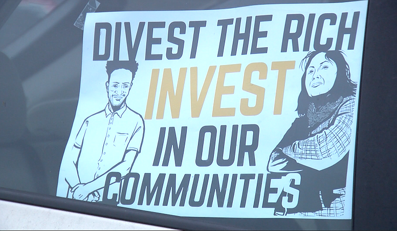 A sign in a car that was part of a protest against widening inequality in Cal...