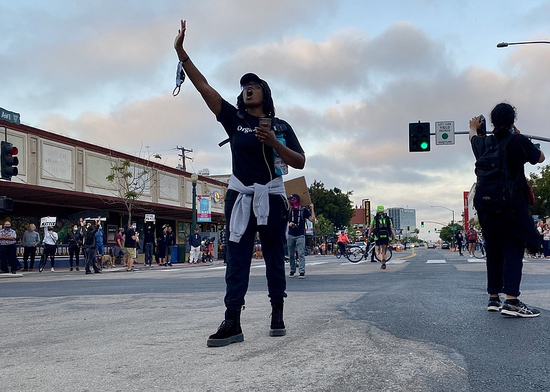 Rashanna Lee holds up her hand and shouts to direct demonstrators on a march ...