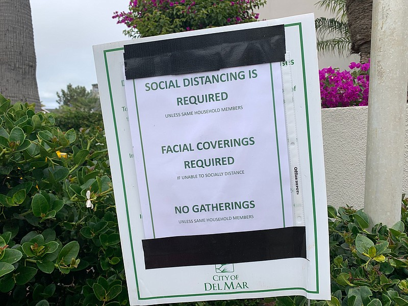 A sign reminding beachgoers to social distance and to wear facing coverings i...