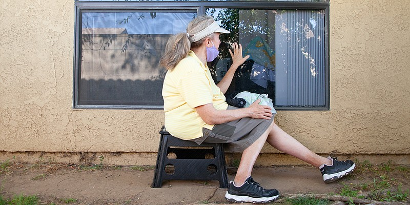 Rosa Montiel sits outside of her sister Lilly's window at San Diego Post-Acut...