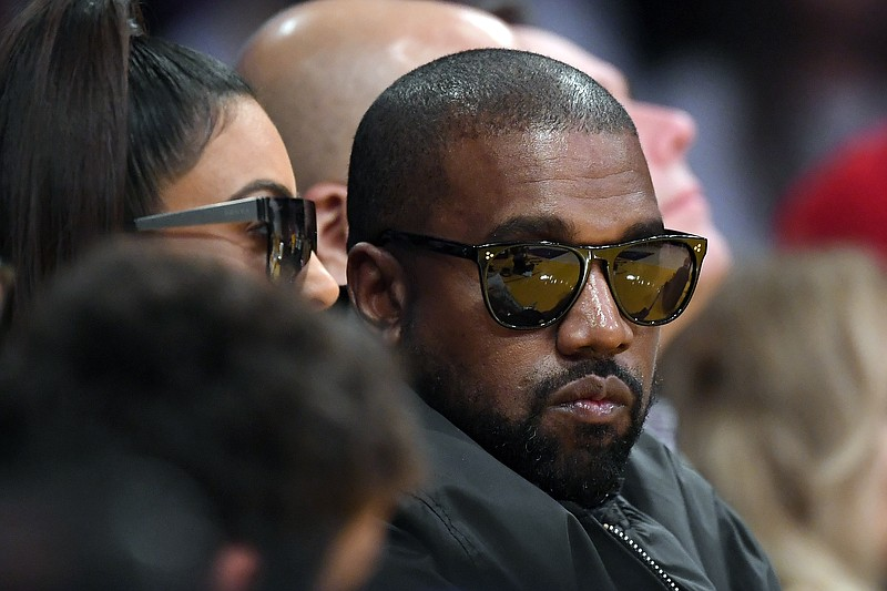 Kim Kardashian, left, and rapper Kanye West watch during the second half of a...