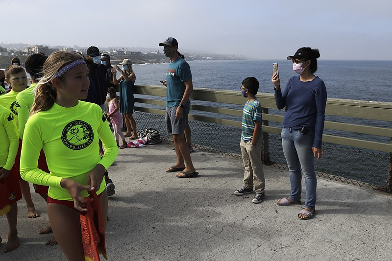 Parents wearing masks look on as San Diego junior lifeguards prepare to jump ...