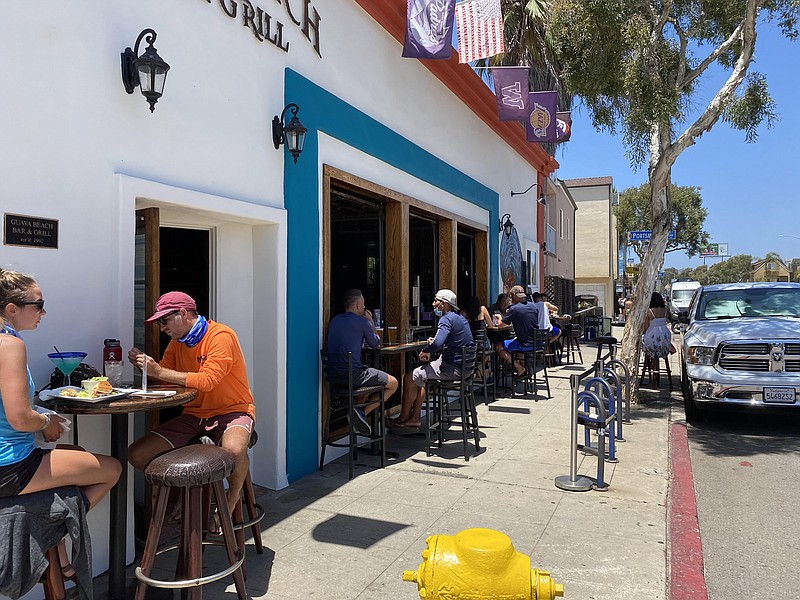 Customers dining on the sidewalk in front of Guava Beach Bar and Grill in Mis...