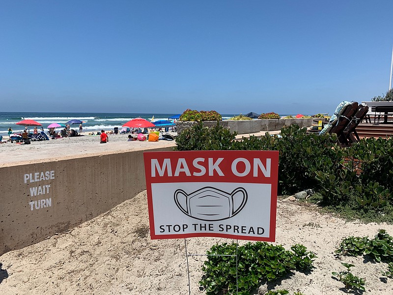 A sign requiring face covering is pictured at a beach in San Diego, July 10, ...