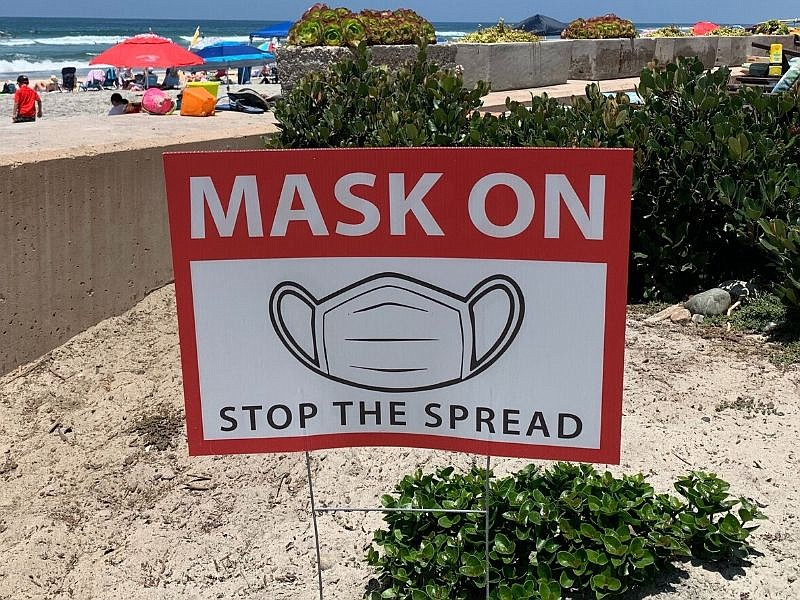 A sign in the sand encourages beachgoers to wear masks in Del Mar, July 10, ...
