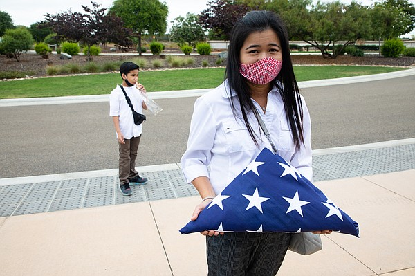 Witchelda Bondoc holds the flag presented to her during t...
